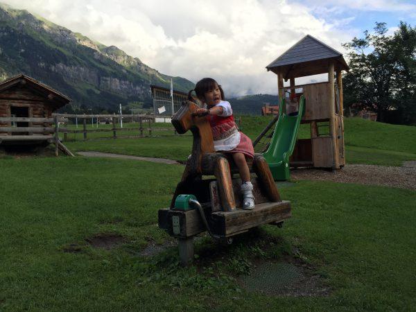 Wengen村の公園の木馬で遊ぶ娘。2000m級のメンリッヘンの山をバックに気分はハイジ?!